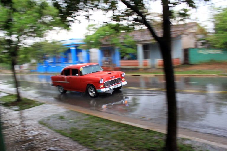 Old-American-car-drives-through-heavy-rain-in-Vinales,-Cuba